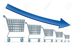 Sales decline symbol as a group of shrinking shopping carts with a blue arrow going down as a metaphor for commercial retail consumerism on a white background.